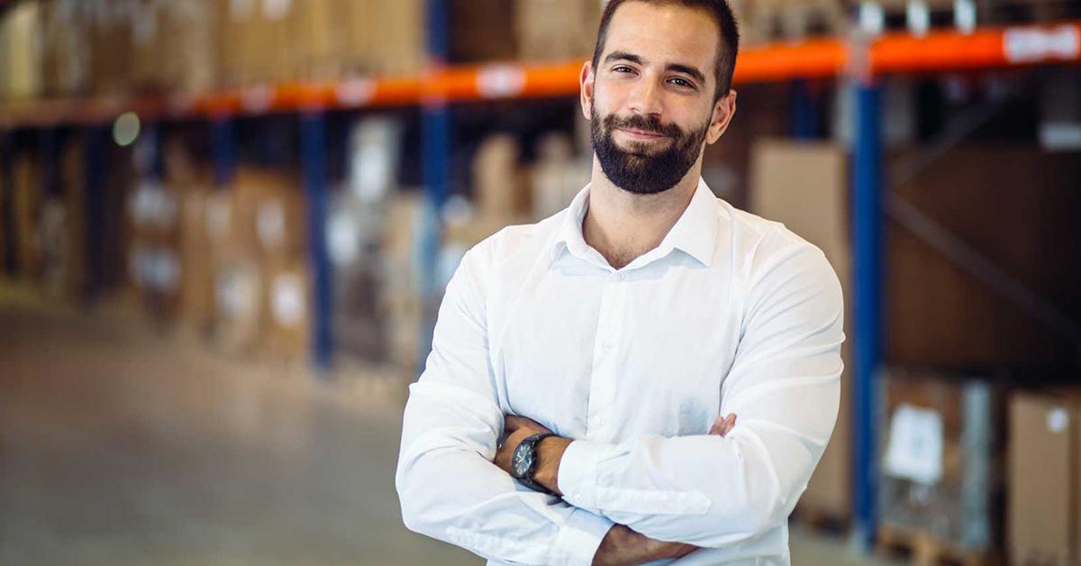 Homem branco sorrindo e de braços cruzados. Ele tem barba e cabelos curtos acastanhados. Ele está vestindo camisa social branca e um relógio no braço esquerdo. Ao fundo da imagem, há um galpão de estoque, em área de Logística.