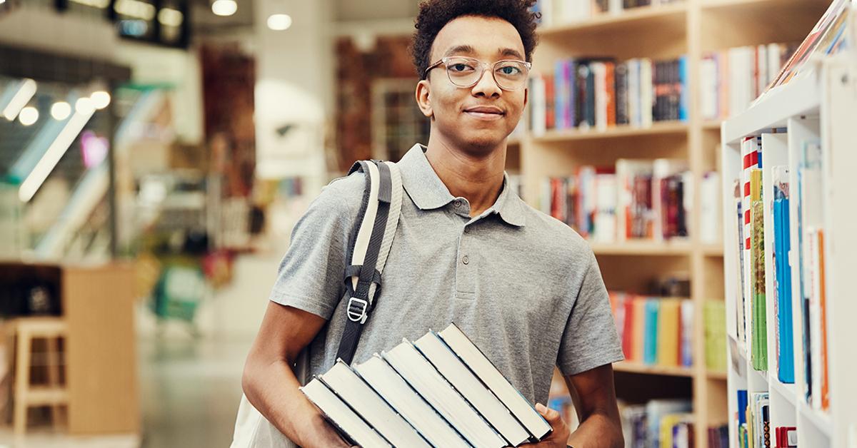 Ao centro da imagem homem negro segurando uma pilha de livros, em uma livraria. Ele veste camiseta cinza e usa óculos de grau. Ao fundo, há livros de direito, mesa de madeira.