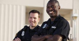 dois policiais sorrindo. À frente, há o policial negro e ao fundo, um policial branco. Os dois estão de lado, levemente inclinados para frente.