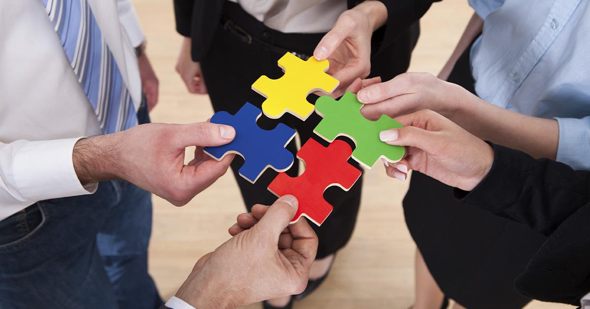 quatro mãos, sendo que cada uma segura uma peça de quebra cabeça. As peças estão quase encaixadas.