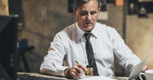 Ao centro da imagem, homem pardo está sentado frente a mesa. Ele, que veste camisa social branca e gravata preta, usa distintivo de polícia. Seu rosto está ligeiramente inclinado para a mesa, em que estão documentos, computador, teclado, xícara, caneta e outros. Ele segura uma caneta com a mão direita e um papel com sua mão esquerda. O fundo está desfocado.