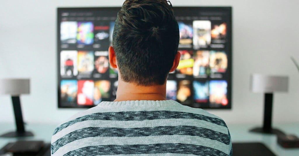 No centro da imagem um homem de costas. Ele, que tem cabelo castanho curto, veste blusa de frio com listras horizontais nas cores cinza e preto. Ao fundo da imagem, em seu centro a uma televisão com uma amostra de filmes. Em ambos os lados da TV, a um abajur.