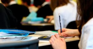A imagem mostra a silhueta de uma pessoa branca. Ela segura um lápis preto e está a escrever em um papel sobre uma carteira, a qual está repleta de livros e cadernos. Há também uma calculadora. Ao fundo, muitas pessoas sentadas em carteiras.