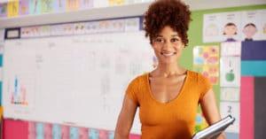 mulher negra à frente, da cintura para cima, ela veste blusa laranja. Ao fundo, quadro branco.