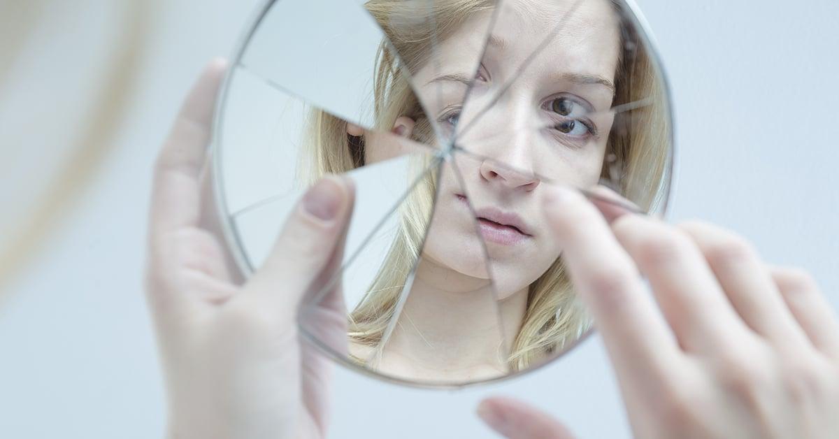 imagem de uma mulher branca e loira em um espelho quebrado. Ela segura o espelho com a mão esquerda e toca a imagem com o dedo indicador da mão direita.