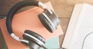 um headphone reto em cima de papeis rosa e azul em cima de uma mesa de madeira. Ao lado um livro aberto.