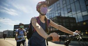 À frente mulher anda de bicicleta. Ela está com blusa cinz escuro, máscara e capacete. Atrás, homem anda de bicicleta. Ele está de camiseta, bermuda, máscara, óculos e capacete. Na lateral da extrema direita há uma grande prédio espelhado.
