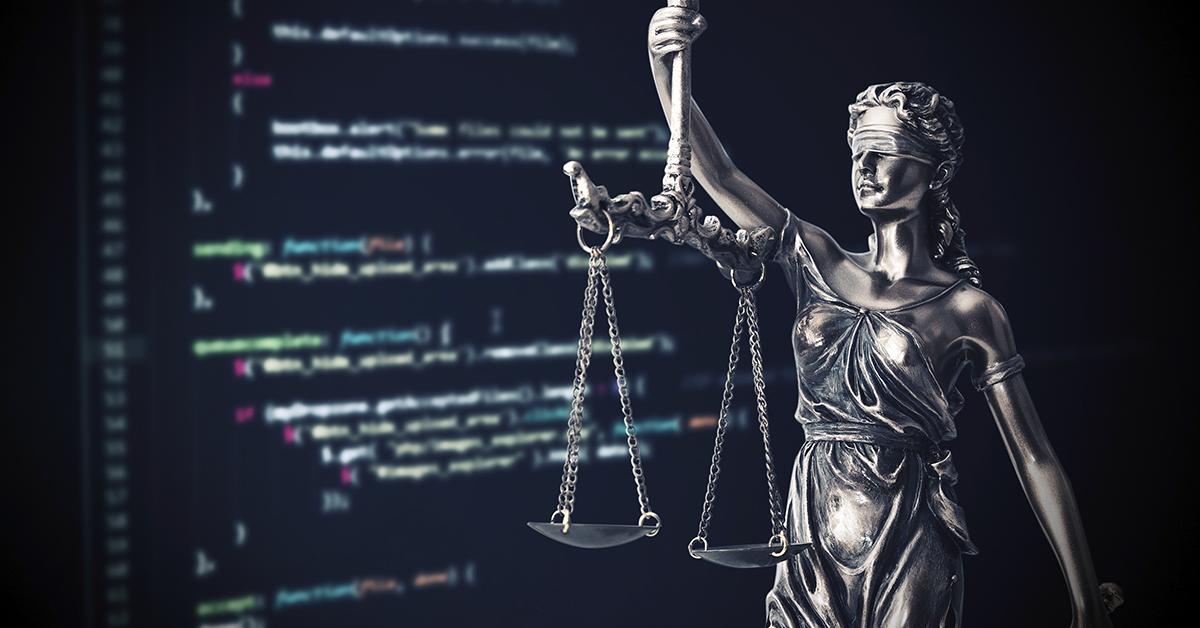 Ao fundo tela de computador, à frente estátua da justiça.