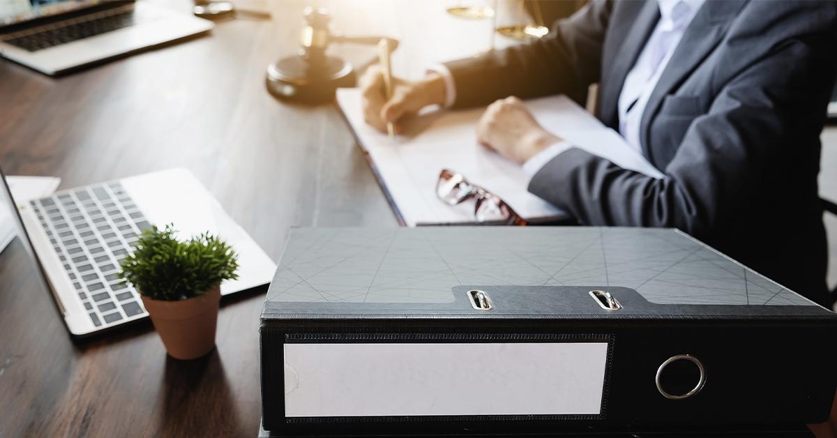 a imagem mostra uma mesa de madeira com vários artefatos, como fichário, notebooks, vaso com planta, malhetes. À direita da imagem, uma pessoa enquadrada do abdômen ao pescoço. A pessoa, que veste camisa e paletó, está a escrever em um caderno. Seus óculos repousam ao lado.